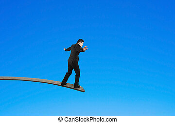Businessman balancing on wooden board with blue sky