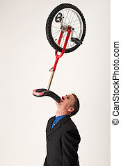 Businessman balancing unicycle