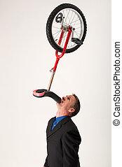 Businessman balancing unicycle
