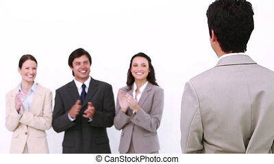 Businessman being congratulated by colleagues