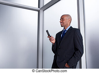 Businessman beside a window looking at cell phone