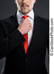 Businessman. Bossy young men adjusting necktie while standing isolated on black