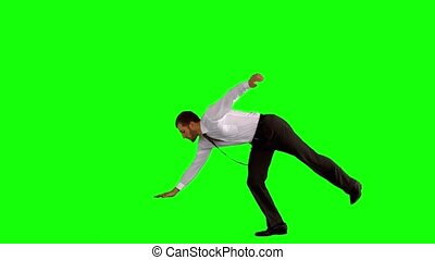 Businessman break dancing on green screen in slow motion