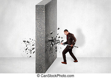 Businessman breaking wall of obstacle by hitting it with sledgehammer. Business challenge conquering adversity concept