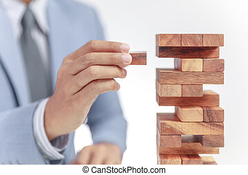 businessman building tower of wooden blocks