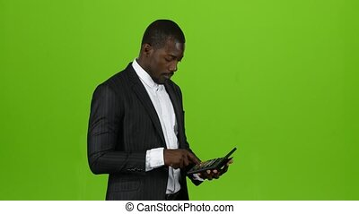 Businessman calculates his income on the calculator, he is bankrupt. Green screen