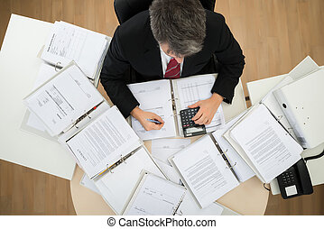 Businessman Calculating Bills - High Angle View Of...