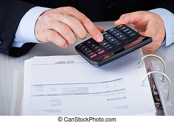 Businessman Calculating Finance In Office