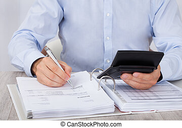 Businessman Calculating Financial Expenses - Midsection of...