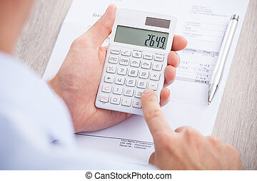 Cropped image of businessman calculating invoice at desk