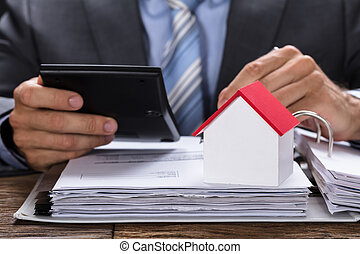 Businessman Calculating Invoice With Model Home On Documents
