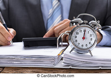 Businessman Calculating Invoice With Alarm Clock On...