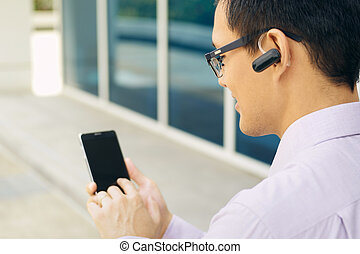 Businessman Calling On Mobile Phone With Bluetooth Headset