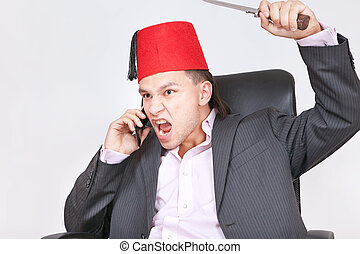 Businessman calling on phone and holding knife