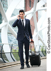 Businessman calling on phone and traveling with bag at metro station