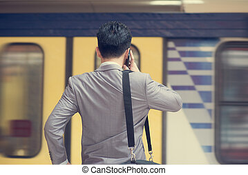 Businessman calling on phone at train station.