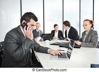 Businessman calling on phone, business meeting at background