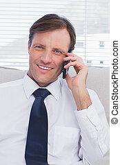 Businessman calling while smiling at camera