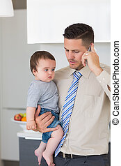 Businessman carrying baby boy while using mobile phone