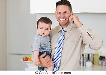 Businessman carrying baby while while using cellphone -...