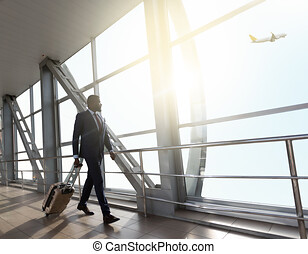 Businessman carrying baggage, moving to boarding gate in airport