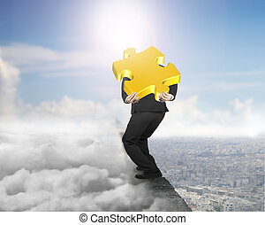 Businessman carrying gold jigsaw puzzle on ridge with cloudscape cityscape