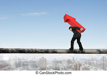 Businessman carrying red arrow sign balancing on tree trunk,...