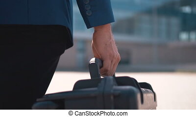 Businessman Carying Case - Back close up view of businessman...