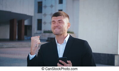 Businessman celebrating success. Man received a message with good news. Successful Businessman showing Yes gesture, extremely happy about good news from smartphone. Office building background.