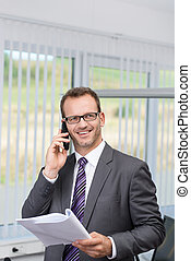 Businessman chatting on his phone in the office