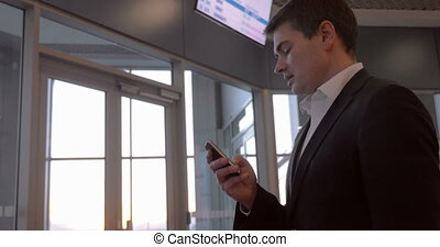 Businessman chatting on the phone at airport