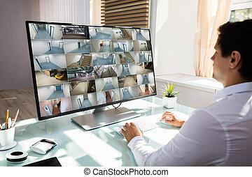 Businessman checking CCTV camera footage on computer