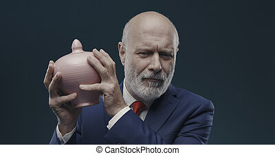 Businessman checking funds in the money box, investement and banking concept