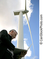 Businessman checking his laptop under a wind turbine