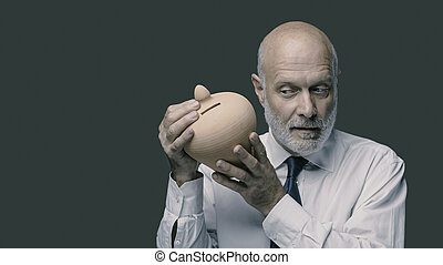 Senior businessman checking his savings in a clay money box, he is shaking it and listening, investments concept