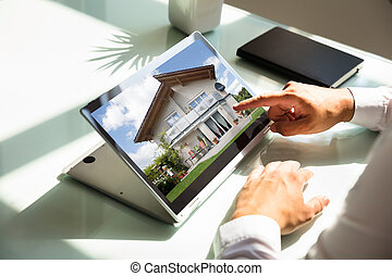 Businessman checking house on laptop