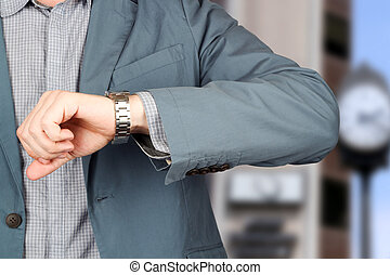 businessman checking time on his watch .