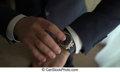 Businessman checking time on his wrist watch, man putting clock on hand, groom getting ready in the morning before wedding ceremony