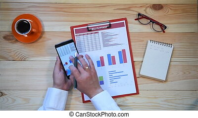 Businessman Using Mobile Phone And Checks Start Up Statistics. Business Concept
