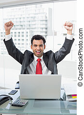 Businessman cheering in front of la - Portrait of a...