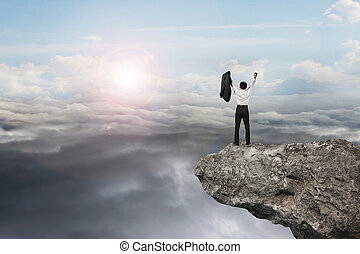 businessman cheering on cliff with natural sky daylight...