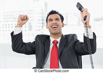 Businessman cheering with telephone receiver at office -...