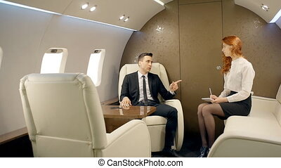 Businessman chief instructing young lawyer female intern in private jet. Male boss in black suit sitting on confortable seat, talk and gesticulating actively. Woman with red hair, in white shirt taking notes on sofa opposite to him.