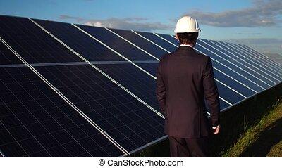 Businessman choosing alternative energy, walking at solar energy station.