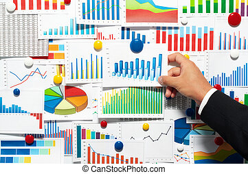 Businessman choosing from a variety of graphs.