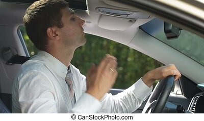 Businessman cleaning lipstick from cheek in car