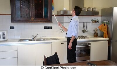 businessman cleaning the furniture in the kitchen