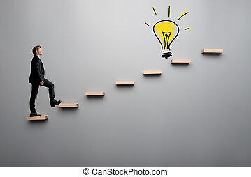 Businessman climbing steps towards light bulb