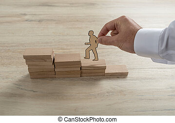 Businessman climbing the steps to success with paper silhouette cutouts of a man