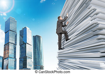 Businessman climbing up a huge stack of paper